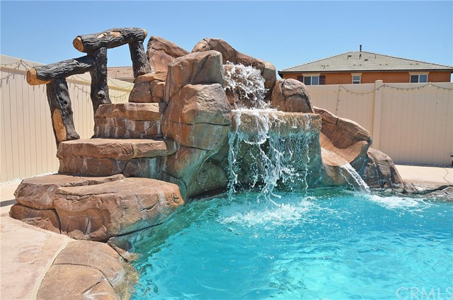 Just move in and enjoy!  Salt Water Pool Home! This spacious salt water pool home with a beautiful rockscape waterfall and slide, built in BBQ, built in gas fire pit, features 4 bedrooms and 3 bathrooms. The open floor plan and large backyard is great for entertaining. All the bedrooms are upstairs with a large loft. The Master bedroom features two closets and the whole house has plantation shutters. The front yard is low maintenance with turf and rock scape that was recently installed and the backyard is an oasis with a large water fall and slide feature that is next to the spa with rock scape upgrades a gas fire pit and BBQ island. The large patio stretches across the house with 3 fans to cool your guests. The Kitchen has a deep sink and water filtration system. The home has a complete sprinkler system that is currently capped off, so sprinkler system is there if ever needed. This home is turn key and ready for you. The home also offers a fire sprinkler system on both levels.