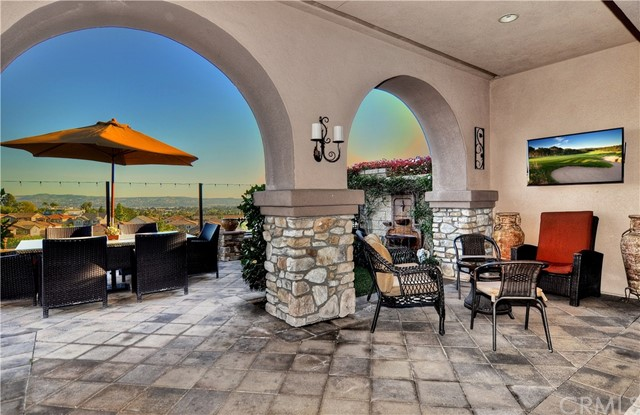 REDUCED $100,000 FROM ORIGINAL LIST PRICE.  Situated in one of Yorba Linda's finest neighborhoods, this stunning toll Brothers property in the Heritage development of Vista Del Verde.  This home sits at one of the highest points on Via Roma with spectacular views of city lights and Catalina Island. Enter through the grand entryway with a diamond medallion centerpiece. The walls are intricately hand painted and an elegant chandelier drops from the high ceilings. A separate wine room, which can easily be converted into a living room or office, sits across from a formal dining room that has hand painted murals by Darren Corrigan. The kitchen is fit for a chef with gourmet professional Kitchen Aid appliances, including a 42 inch built in stainless steel refrigerator and double oven. Dramatic five panel stacking glass walls extend the family room into the outdoors. The grounds offer a custom slate serving bar with refrigerator, professional Viking BBQ, TV, fountain and paver accented patio. An ornamental iron bannister is eye catching as you make your way to the four well-appointed bedrooms. The master offers a balcony to relax and enjoy the views. The master bath has a king size tub, granite counter-tops, dual sinks and vanity and a beautifully designed walk in closet. The large bonus room is ideal for a home theater. Home is beautifully upgraded!