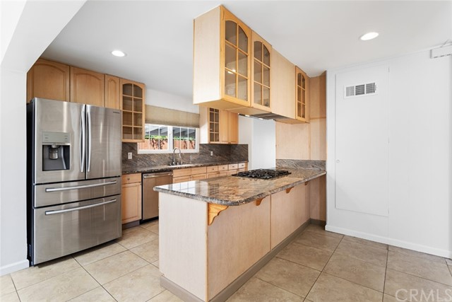 Kitchen with custom made cabinetry, with sleek gourmet granite counters.