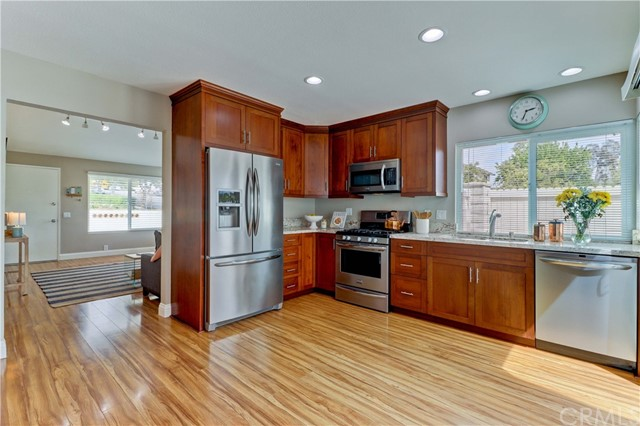 Kitchen with custom cabinets, granite countertops, stainless steel appliances, lots on natural light and view of trees.