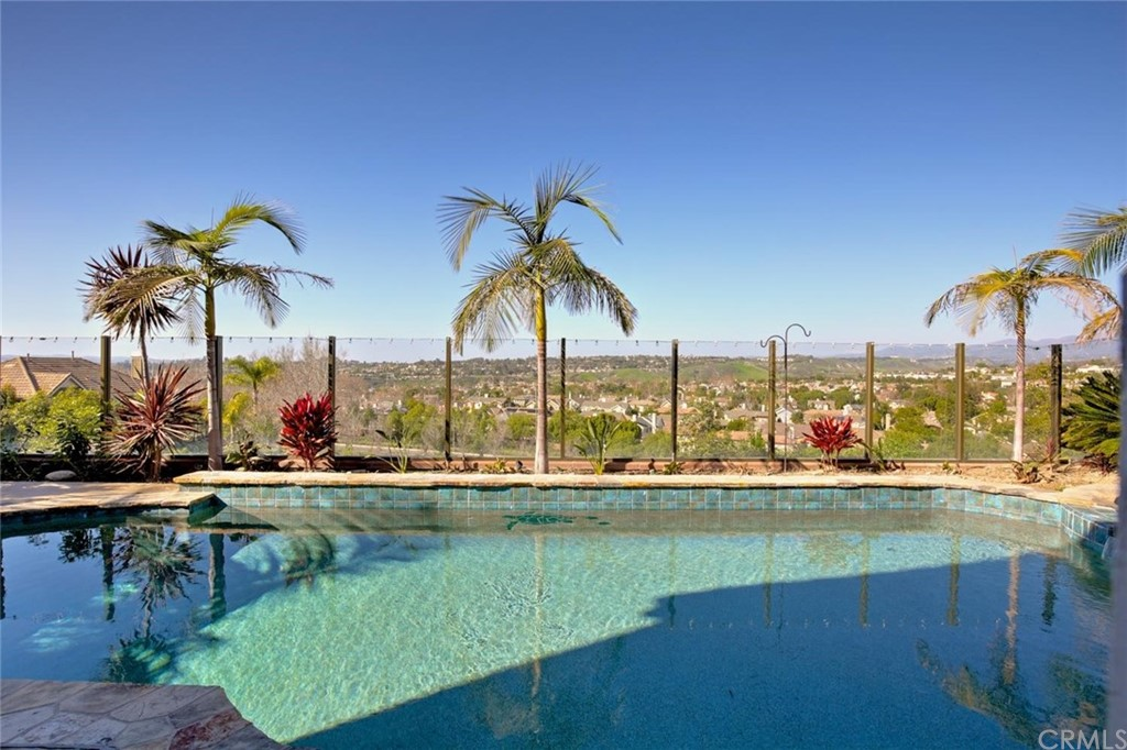 VIEW AND A POOL?  YES!   The minute you walk from the tree-lined street and enter the front door you will be entranced with the incredible view from this lovely home. You will immediately notice the wall of windows overlooking the swimming pool and unobstructed views of open skies and rolling hills.  The pool has a new water heater that was just installed and a built in bbq and bar area.  This is the perfect yard for entertaining or just enjoying the evening sunsets.  Beautiful upgraded flooring (wood look tile) flows through the spacious floor plan of the downstairs offering a stunning backdrop for the custom wainscoting and newly updated kitchen with quartz countertops and glass backsplash. The breakfast counter and dining area share the open floor plan of the family room, featuring a built in entertainment area with plenty of storage and natural light. This room shares a two-sided fireplace with the den.  This downstairs den could easily be converted to a 5th bedroom/office and even has a set of double doors that lead to the backyard. Conveniently located off the den is a full bathroom complete with walk in shower. Upstairs has a good sized laundry room with a sink.  At the top of the landing you'll love the  built in desk area adjacent to a deck off the front of the home. Enjoy the sunset views from a spacious master bedroom with dual closets, double vanity and upgraded flooring. Nestled in the heart of desirable Flintridge Village, this beautiful home is minutes from shopping, restaurants, parks and schools as well as Chaparral Elementary School. Association dues include Cox Internet service. Enjoy Ladera Living with award winning schools, a skate park, water parks, miles of trails and community parks galore.