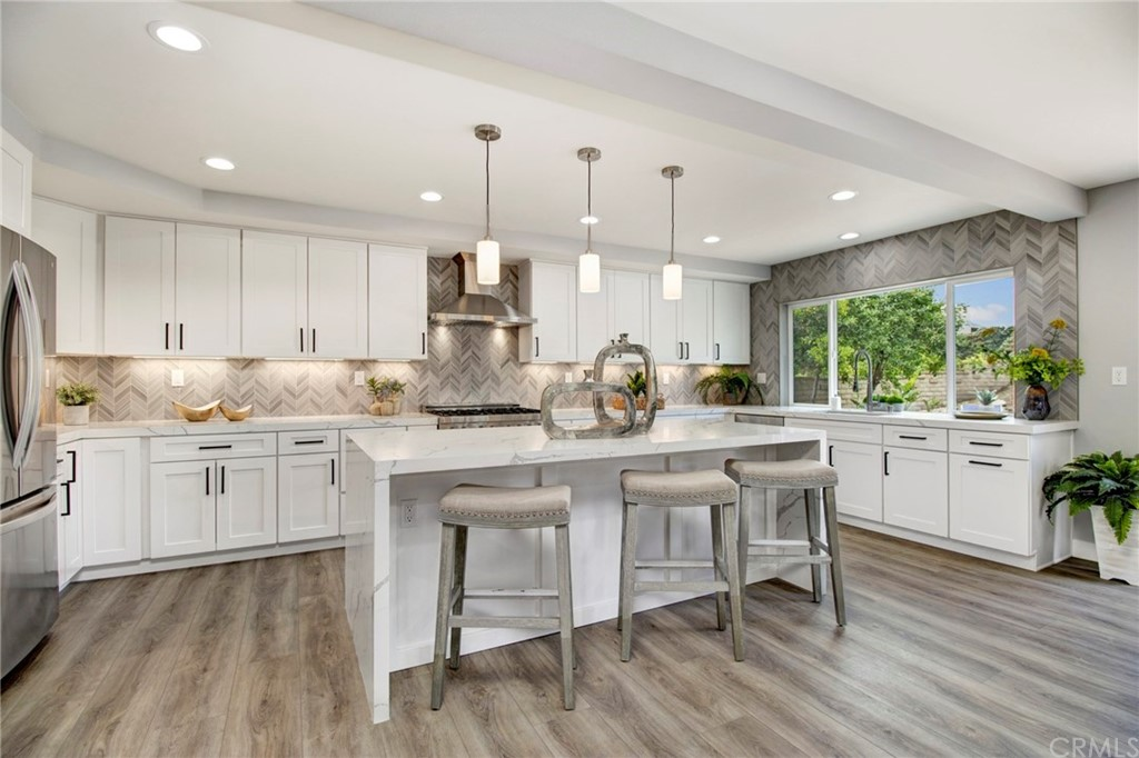 """Extensively Remodeled Custom 5 bedroom, 3 bath home w/900 sq. ft. 3 car garage & workshop. CDS location, flat 10,500 sq. ft. lot w/8' gate to side yard & huge back yard.  Main floor bedroom & large ¾ bath. Open floor plan w/great room concept. Enlarged & reconfigured kitchen w/white shaker cabinets, self-closing drawers/doors & matte black hardware. Calcatta Laza Quartz counter tops & double waterfall island. ALL NEW ZLINE stainless steel appliances, 36"""" Professional Gas 6 Burner Range, Hood, Microwave Drawer & Dishwasher. KOHLER Semiprofessional brushed nickel faucet, under cabinet lighting & blown glass pendant lights.  Reconfigured & Remodeled Master Bath w/ barn door entry, 6' x 6.5' wet room surrounded in 24"""" x 48"""" marble look tile, frameless glass enclosure, free standing tub w/matte black freestanding faucet.  90"""" white shaker style dual vanity, self-closing drawers/doors, Calcatta Laza Quartz counter top, square black framed mirrors, recessed lighting & blown glass pendant light, & matte black hardware, faucets, shower valve, shower head & matching towel bar. Large walk-in closet.  All remodeled & highly upgraded bathrooms.  Oversize indoor laundry room w/shaker cabinets, quartz counter tops & laundry sink.  ALL NEW dual pane vinyl windows/doors, PEX repipe, paint in/out, ext/interior doors, base, case, hardware, lighting, sprinkler system, sod, landscaping.  9"""" plank waterproof flooring throughout.  Complete list of improvements available in the listing supplements."""