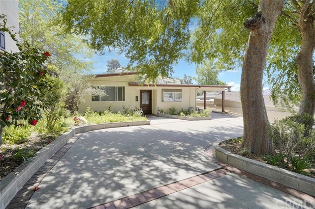 Easy and stylish living awaits with this comfortable La Crescenta residence you'll love coming home to. With easy-care tile and hardwood-style flooring throughout, a lifestyle that requires minimal maintenance is all yours. The inviting open-plan design gives you large gathering areas to choose from with French doors leading to the open patio. Double paneled windows block most of the noise coming from nearby streets and freeways, making it a quiet space to live in.   Your attractive and homey kitchen is galley-style and offers stainless steel appliances, see-through cabinet doors, and granite countertops and backsplash. All three of the well-sized bedrooms have vaulted ceilings and mirrored closet doors. Both baths are tastefully done, and you'll have the added convenience of a laundry room. Want more space? You have the option of building an ADU in the back to either generate more income or offer accommodation to guests. You'll enjoy the convenience of a circular driveway and have gated parking along with two carports. Set in a prime and coveted location, this ideal home is near amazing schools, eateries, and convenient shopping options. All this and more could be yours if you act fast, so come take a tour while it's still available!