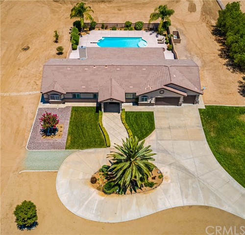 "Looking for large, FLAT horse property w/huge RV Garage, sparkling pool & spa, mountain views, upgraded 4BD-3BA & 4 car garage...then check out this ultimate single story pool home on 2.82 acres! This 100% useable lot is cleared & ready for your horses, livestock, RV, Boat, guest home & all of your toys! Offers fully enclosed RV Garage & workshop (apprx 24'x48') that has endless possibilities. This beautiful custom single story has an open floor plan, vaulted 12' ceilings (apprx), 9' doors (apprx), Plantation Shutters, built in shelving, exquisite tile flooring, custom fixtures & ceiling fans throughout. Offers Granite w/tile accents in the kitchen & all bathrooms. Has formal Dining Room, large Living Room, separate Family Room w/fireplace & large bedrooms (one w/Murphy bed). Dual Primary Suites have their own bathrooms, granite counters & dual sinks, walk-in closet & sliders to their own private porches. Gourmet Kitchen has plenty of cabinetry, granite counters, tile backsplash, stainless appliances, instant hot water & grand center island. Oversized 4 car tandem ""finished"" garage is perfect for the auto/motorcycle enthusiasts! Also, includes paved circular driveway, manicured landscape, dual gated entry, huge rear covered patio & custom hardscape w/fire pit. The Olympic Size pool & spa are the icing on the cake. All this w/NO H.O.A, low taxes, access to horse trails & prime Cul-De-Sac location! Must see to appreciate this beauty!"