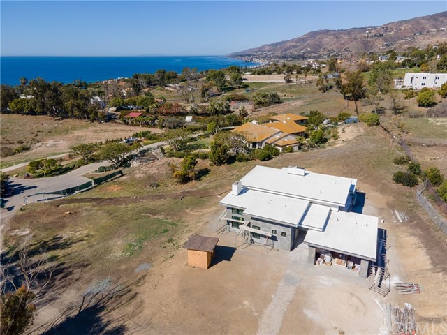 Enjoy the rewards of a newly constructed custom home and the advantages of living in an established neighborhood at this soft-contemporary residence in Malibu's enviable Malibu Park enclave. Settled on an elevated homesite of nearly 2.54 acres, the open and bright single-level design frames panoramic ocean and hill views that complement most living areas. Clerestory windows, 15' ceilings and an open-concept floorplan enrich both entertaining and everyday living throughout the home, which features 3 bedrooms and 3 baths in approximately 2,500 est. sq. ft, including a guest room. A pivoting mahogany entry door leads to an impressive foyer that introduces a dramatic living and dining room area with bi-folding glass doors, linear 7'-wide fireplace with stone surrounds all of the way to the ceiling. Centered around a marble island, the chef-inspired kitchen hosts a walk-in pantry, Dutch door leading to the spacious backyard patio, custom cabinetry, high-end countertops and Bluetooth enabled smart appliances. Wood flooring, an abundance of recessed lighting fixtures, and top-tier fixtures and finishes grace the residence with timeless style. Relax and enjoy views of the Pacific in a master suite with fireplace, a walk-in closet, and a spa-caliber bath with soaking tub, separate shower and dual sinks. Home is perched at the top of a cul-de-sac with only 2 neighboring properties. A private road with circular motor court accommodate guest parking. The attached garage holds 2 vehicles.