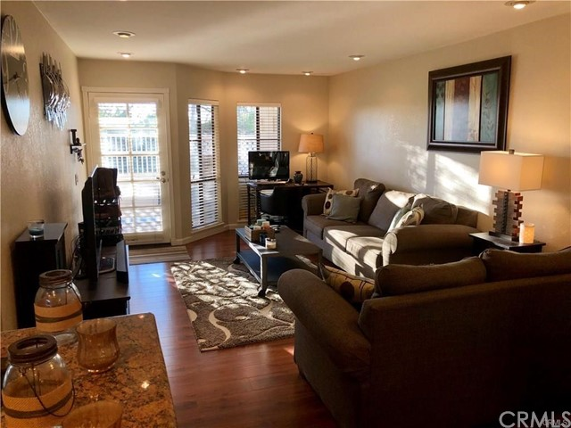 LOCATION!! LOCATION!! LOCATION!! Great Opportunity to own this single level condo with privately gated front patio with white fencing. Kitchen features granite countertops, gas stove, dishwasher, and built in microwave. Large living area with dining room combo with ceiling fan. Large sliding glass mirrored doors with plenty of storage. Spacious bedroom with mirrored wardrobe doors and ceiling fan. Upgraded interior doors, new laminate wood floors, ceramic tile flooring in bathroom. Inside Stackable washer and dryer included! HOA paid by landlord and includes Water, Trash, and Fire Insurance and will maintain exteriors. This beautiful community features 2 community pools, a spa, playground and many green belts. Located close to shopping, freeways, restaurants, golf, and parks!