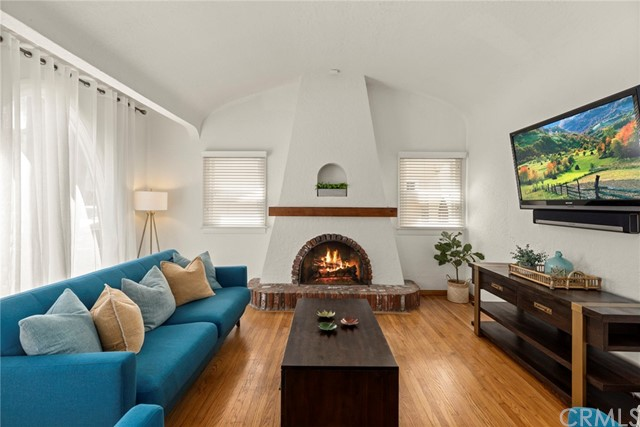 Light and bright living room with beautiful Spanish architectural features such as large arched front window, barreled ceilings and brick plaster fireplace....