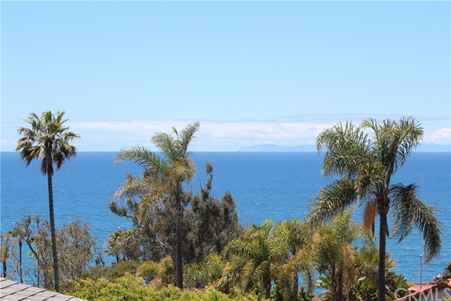 Enjoy panoramic ocean and Catalina views from this 2 bedroom and 2 bath home situated in Laguna Viillage! Middle unit with living space on one level. The kitchen has a breakfast bar, refrigerator, and opens to the dining area and living room with wood-burning fireplace and views!  Shows light and bright with a spacious wrap-around deck with ocean breezes and ocean/sunset views. Includes a carport plus one parking space parked tandem.  Separate storage area with coin laundry to share with 2 other units. Great location close to restaurants, shopping, and close to one of Laguna's most desirable beaches, Victoria Beach!