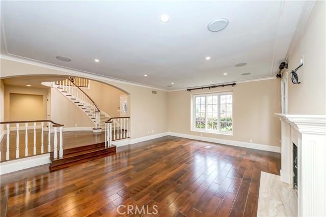 Step down main living room includes built-in speakers, hardwood floors, fireplace
