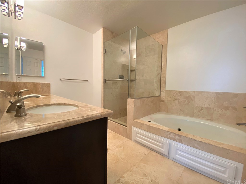 Suite bath with separate spa tub, walk-in shower and toilet room