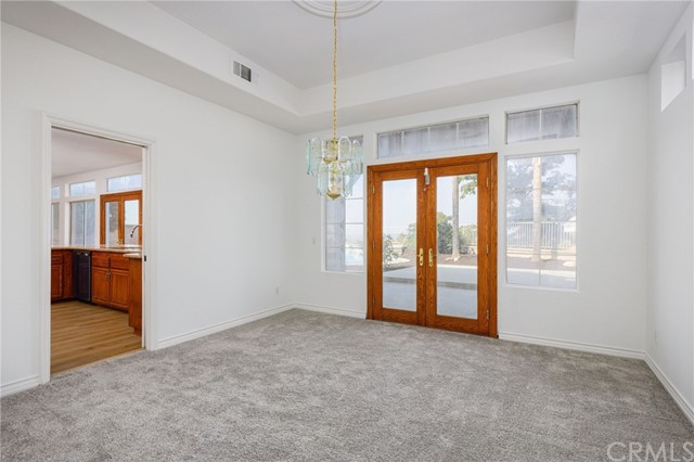 Formal Dining room with double wooden patio doors and a pocket door leading into the kitchen.