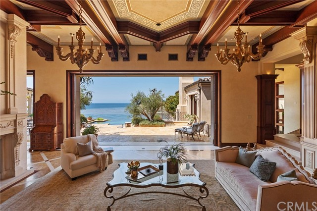 The grand living room opens to the patio and infinity pool/spa with coastline views