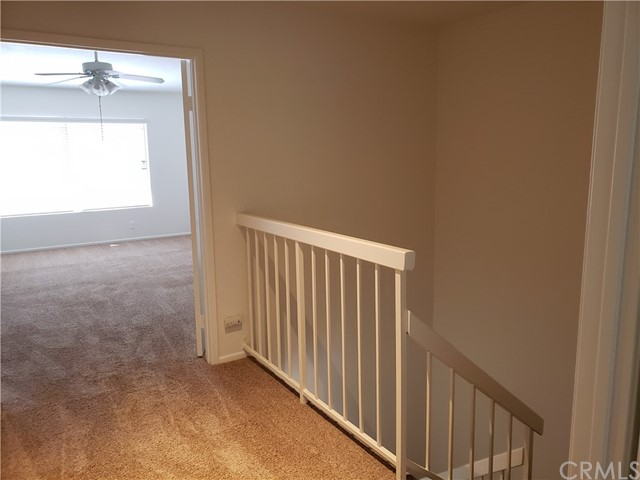 Upstairs landing...looking at one of the master suites with a ceiling fan.