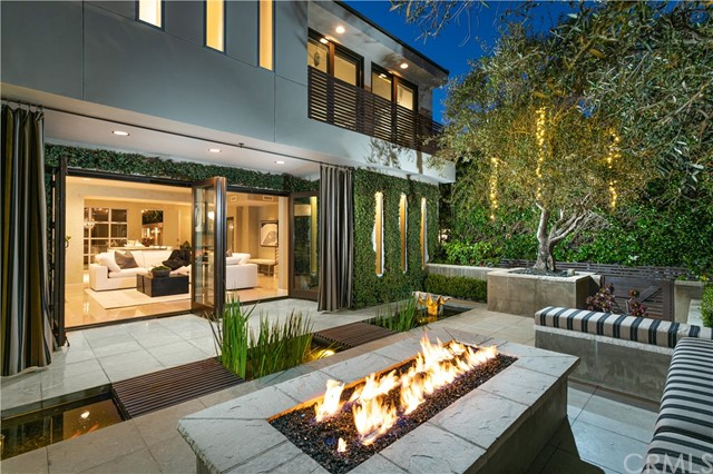 Balinese flair located in the exclusive Corona Del Mar Village. This zen 3 Bed plus Office home embodies Southern California's modern seaside living. Designed for entertaining, the residence seamlessly blends modern indoor/outdoor living from an open, oversized 33' wide location with contemporary coastal finishes. A tranquil front entryway patio with a Koi Pond, Olive trees, and fire pit leads to two sets of french doors combining the main open living space with a broad front veranda. Savor the entertainer's kitchen complete with a 10-foot center island, skylights above, a temperature-controlled wine cellar, and a generous dining area. Off of the kitchen is a restaurant-inspired central courtyard with Pizza Oven, water feature, and bar seating. Upstairs, wide hallways lead to an en-suite bedroom, office space, and a luxurious primary retreat highlighted by dual sliding glass doors, fully electronic window shades, and a dual-sided fireplace. The oversized primary bath features dual sinks, a sunken tub, separate walk-in shower, and streaming natural light from skylights above. On the third level, another beautifully appointed en-suite bedroom leads to an outdoor turf-covered sundeck for unwinding. Stunning interior finishes include Venetian Plaster, oak wood floors, granite counters, and travertine flooring. With a Walk Score of 88, convenient shopping, bespoke restaurants, breathtaking ocean vistas, and world-class beaches just outside your door this home checks all the boxes.Balinese flair located in the exclusive Corona Del Mar Village. This zen 3 Bed plus Office home embodies Southern California's modern seaside living. Designed for entertaining, the residence seamlessly blends modern indoor/outdoor living from an open, oversized 33' wide location with contemporary coastal finishes. A tranquil front entryway patio with a Koi Pond, Olive trees, and fire pit leads to two sets of french doors combining the main open living space with a broad front veranda. Savor the 