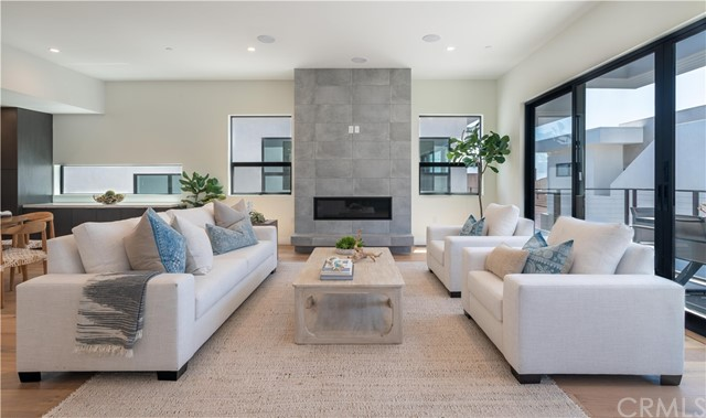 Statement fireplace centers the living space with adjointing balcony (shown here staged)