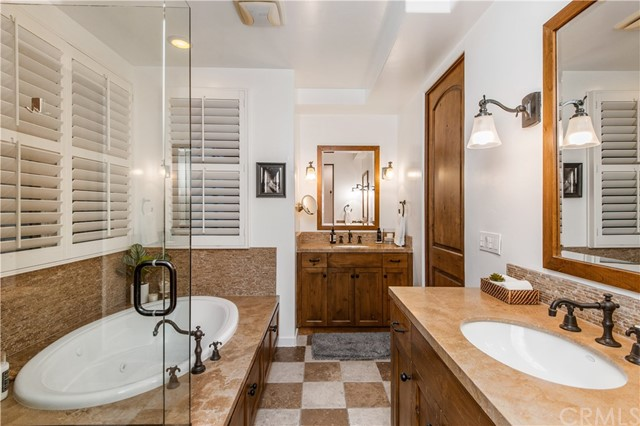 Master bathroom features a spa-like tub, dual vanities, private water closet and a walk-in shower.