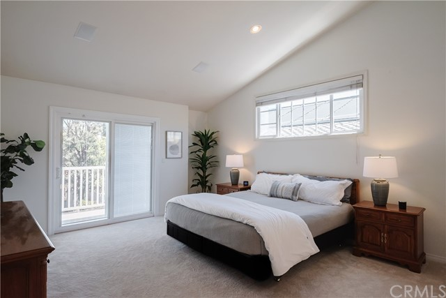 Spacious Primary Suite with vaulted ceiling, sliders to deck overlooking back yard.