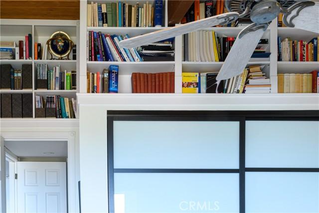Custom built-in bookcases in second bedroom hiding storage area behind