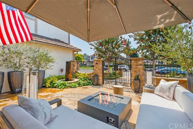 Large front patio, view out to the street. Notice the modern style fire pit with crushed ice FireGlass, pots & fountain