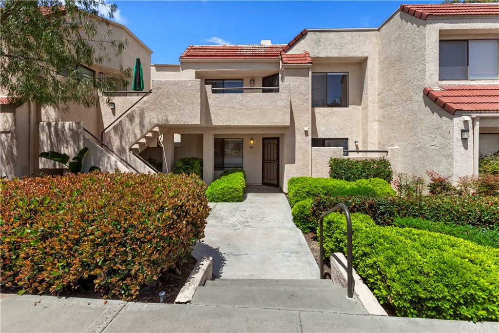 Beautifully maintained upper level unit in Crystal Cay Community, part of Laguna Heights.  This spacious single level, 2 bedroom, 2 Bath condo is the larger model in the Community with a storage room in the gated front porch.  Entertain from this open floor plan with updated kitchen open to the living/dining room.  This open and bright unit boasts cathedral ceilings, skylight & ceiling fan.  Enjoy rich wood laminate flooring, tile fireplace with mantle & gas fire logs.  The master bedroom includes a private tub/bath, secondary bedroom the bath is just off the hall, along with the laundry closet with stack washer/dryer.  Refrigerator & microwave are also included. The carport is within the building, fully covered with a storage area overhead.  Community has 2 pools/2 spas and is well located near schools, shopping, hiking & biking trails, beaches & freeways!