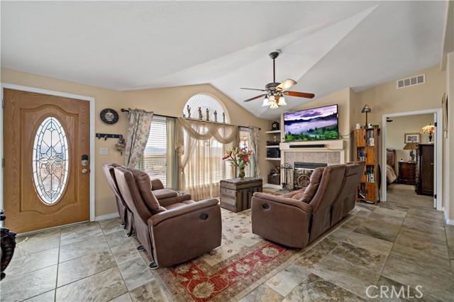 Main living room w custom door, ceramic tile flooring, fireplace and ceiling fan/light fixture.