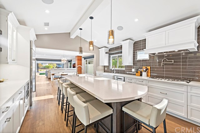 Gourmet chef's kitchen with vaulted ceilings has been renovated with huge island and breakfast bar has been renovated with top of the line finishes.