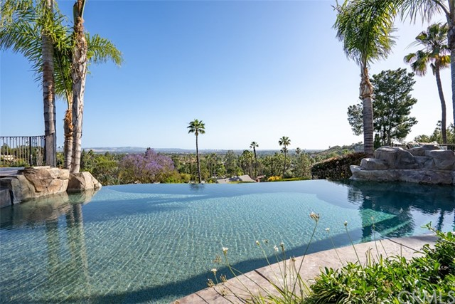 Located in the most prestigious part of North Tustin, this luxurious, gated property is its own private resort. Enjoy panoramic views all the way to Catalina Island from almost every room in the house. Gorgeous sunsets are framed by palms as a fiery orange and red glow blazes over the distant hilltop. Start the day with a sunrise soak in the spa and ease into the day as the sun paints the sky in an everchanging palette of vibrant color. Spend a relaxing weekend floating in the pool while gazing past the infinity edge toward a backdrop of rolling hills, majestic trees, and endless skies. Staycations have never felt so right. Plus, this house is just made for entertaining. Host an evening cocktail party under the covered patio and serve up gourmet food and drinks while guests marvel at the stunning panorama of city lights. This will be THE place to invite the kids' entire sports team over for a victory celebration. The kids will love swimming in the pool, playing cornhole on the lawn, or making the perfect trick shot at the billiards table. For a quiet night in, cozy up to the warm glow of a crackling fire in one of three fireplaces, or just read a favorite book on the large viewing balcony as the whole world just melts away into a vista to infinity and beyond. For large families or buyers with a few collector classics, there is a three-car garage with an EV charger plus a fourth garage/shop to hold the big toys. Gated RV/boat parking. No HOA/Mello-Roos. Award winning schools.