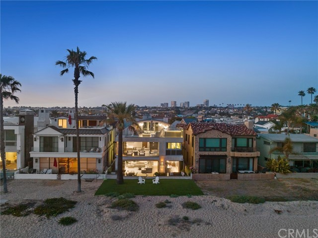 """A sensual oceanfront contemporary residence that melds stunning architectural detail with intoxicating whitewater views, unfolding as a seamless expression of high-style waterfront living. Masterfully conceived by Oatman Architects and sited on a striking oceanfront lot within the prestigious Balboa Peninsula Point neighborhood of Newport Beach, this exquisitely appointed home glistens with its tasteful use of glass, steel, stone, and wood. Sleek floor to ceiling walls of glass vanish to the side and invite explosive views of the shoreline and infamous """"Wedge"""" from the expansive living, dining and entertaining areas. An artfully designed three-story floating glass staircase ties together the home's principle spaces.  With over 4,000 square feet of living space the residence delivers three impressive en-suite guest accommodations, and a luxurious oceanfront master suite, adjoined by a serene spa bath with steam room shower, Stoneforest free-standing marble soaking tub, and walk-in dressing area. The adjoining private terrace basks in a panorama of coastline views. Designed for extraordinary entertaining and uninterrupted indoor-outdoor living the home's dazzling third level bar/living area is comprised of myriad lounging and dining spaces - with a roof top fire pit and hot tub overlooking the shore break below, and a wrap-around deck that captures equally dramatic nighttime views of the sparkling Fashion Island skyline. Additional interior compliments include two powder baths, laundry room, three car garage with built-in work bench area, CONTROL 4 home automation, electronic window treatments, and stereo throughout.  A chic seaside retreat that embraces the sea, sun, and sky."""