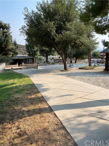 Simply beautiful location for this gem.   The home sits at the rear of the corner lot, with drive access on two sides, making the majority of the property usable. Recently remodeled, the interior is open, fresh and tastefully decorated.  The gourmet kitchen affords space for everyone & everything. There are two counter seating areas, a very large island with a stainless farmhouse sink, granite counters, new appliances, and includes a wine refrigerator. Relax in the inviting living room with a cozy fire in the wood burning stove complete with a custom mantel.  The master bedroom has access to the exterior as does the front bedroom. Boasting a split floor plan, the master and second bedroom are on one end and the front bedroom is on the other, which could be the perfect guest room.   Being outdoors at this property means enjoying large shade trees, having a place to keep your RV(s), toys and more.  The three stall barn has plenty of room for tack and storage, the breezeway is concrete with drains and there is an additional concrete pad on the north side of the barn for the horse trailer etc.  The area is great for horseback riding, hiking or just relaxing.  This listing includes two parcels to total the 25700 sq.ft. lot size.