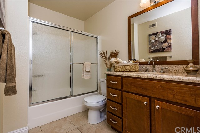 The remodeled hall bath features dark wood cabinets and granite surfaces!