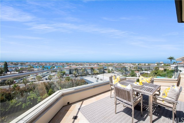 Views from this unique home at the top of the rise on exclusive Kings Road span from Dana Point across Newport Harbor, Catalina, and local landmarks all the way to Palos Verdes in the distance. From the master suite, awake to the sunrise over Saddleback Mountain and at sunset sip drinks on one of three appx. 60 ft. verandas while the evening vistas twinkle from the lights of Newport Center, the Balboa Pavilion, and homes on the harbor's islands. Measuring appx. 5,895 SF, the estate features 3 levels and an open-concept floor plan with high ceilings to ensure that all bedrooms and main living areas take advantage of the views. One of 2 offices, a great room fit with large lodge fireplace, wet bar, and huge gourmet kitchen grace the main level; while the top level delivers a second office with fireplace and a lavish master suite featuring fireplace, private laundry, appx. 350 SF closet, and bath with heated floors and two water closets. A separate family/ media room with full bath and closet (that can be converted to a 4th bedroom), a wine cellar, two guest bedrooms with en suite bathrooms, a second laundry room, and extra storage complete the lower level. The backyard is host to a complete 30 ft. outdoor BBQ/kitchen, grassy area around a custom in-ground spa, and a vegetable/herb garden among lavender and rose bushes; as well as a terraced orchard with lemon, orange, tangerine, apple, and avocado trees. Located moments to the beach, Mariner's Elementary, dining and shopping.