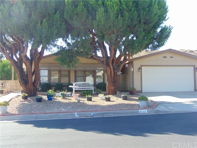 Located in one of Calimesa's desirable senior 55+ community.  You own the land. Curb appeal with park like settings, low maintenance front yard.  This 3 bedroom home, 2 bath, has newer A/C and Hot water heater.  Ceiling fans throughout. Laminate flooring except bathrooms have tile flooring.  Open floor plan, two separate dining areas.  Kitchen has pantry cupboard. Skylight for brightness.  Stainless steel, 4 burner with longer griddle burner in middle of gas stove top. Free standing range.  microwave and dishwasher.  Side by side refrigerator included with easy access water and ice. Arch way entrance to open separate dinning room.  Master bedroom is on opposite side of the home from the other two bedrooms.  Master has large walk in closet, with mirrored doors, soaker/garden tub with separate shower.  Guest bath has larger shower over tub. Bay windows in two guest bedrooms. Individual laundry room. washer and dryer included. Sliding glass door, handicap grab bars,  entrance to Enclosed porch for added living area with bonus room attached for added storage. Fenced breezeway. Long covered front patio, enjoyment while watching the sunsets. Completely fenced back yard, Lemon tree. Two car garage with two work benches, plenty of room for storage.  HOA amenities, salt water pool and spa, Banquet facilities, billiard table, ping pong table, exercise room, library, enjoyment of greenbelts through out the community.  Metered water and sewer is included with the HOA.
