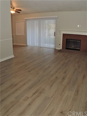 All new modern laminate flooring throughout living areas; brick fireplace; glass sliders to backyard; new blinds throughout.