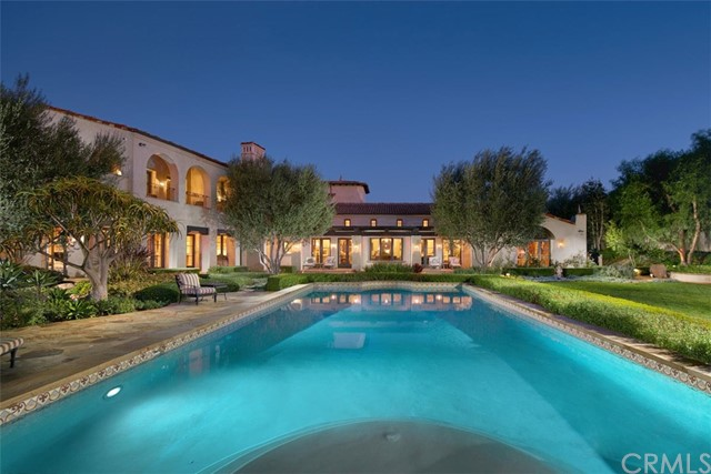 This is one of the finest properties in Orange County — gracing nearly an acre at the end of a quiet cul-de-sac on one of the highest view lots in exclusive, guard-gated Shady Canyon. Designed by architect Cecil Carney and built by the renowned Haigh Builders, the ultra-private residence and guest house span more than 12,000 s.f. of tasteful, livable luxury with panoramic views of the Shady Canyon Golf Course, canyons, hillsides and city lights. No expense has been spared, or detail overlooked, in this magnificent legacy estate. This is a property whose wow factor can't be overstated, starting with the private entry courtyard with Koi pond and bridge leading to the impressive main foyer that immediately reveals the home's exceptional views. The 6 bedroom, 6 and 2 half-bath property (including detached guest casita with kitchenette) features spacious, high-ceilinged rooms that open to inviting sheltered outdoor loggias and terraces and to the spectacular grounds beyond. The main residence encompasses 3 levels with an elevator and includes a sublime master suite with views and dual spa baths; the enclave's most impressive chef's kitchen with secondary catering kitchen and wine cellar; and a lower level with theater and maid's quarters (optional gym). The estate's grounds are unparalleled, with expansive lawns, mature landscaping and trees, swimming pool and spa, water features spanned by bridges, and more. Shady Canyon residents also enjoy world-class community amenities.