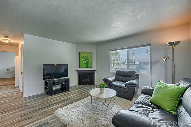 Spacious living room with gas fireplace and wood laminate flooring.