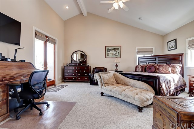 Large master bedroom with vaulted ceilings, featuring a balcony and view to the north and east of snow covered mountains! So beautiful on a clear day!