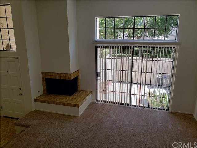 Step into the Living room, with gas started fireplace....Slider leading outside to the brick laced Patio....Newer Carpet in the living room