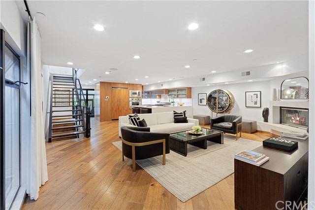 """Welcome to this stunning architectural, end unit townhouse located a few short blocks from Abbot Kinney, Rose, Main St. and the beach. Tucked away on a quiet residential street, this masterpiece is just far enough away from any of the noise and traffic that may come from living near these popular destinations. As you enter the home through the rain glass front door on the main level, notice the 8"""" wide oak plank wood floors that extend throughout and a swanky dining room on the right. This private and versatile room has a modern glass, roll up door that opens to a private patio for the ultimate indoor/outdoor vibe. Utilize this space as a dining room, playroom, home office, gym or however you see fit. The open layout on the main floor is complete with a tastefully remodeled powder room, large, black framed windows that include top-of-the-line designer window treatments and a beautiful fireplace with a smooth concrete surround and mantle. The kitchen has been finished with custom walnut cabinetry, built-in Viking appliances, a full marble slab backsplash, waterfall style quartz counters and roll-out pantry drawers. Upstairs is the enormous master suite, laundry closet and two additional bedrooms that share a jack and jill bathroom with a private water closet. The unforgettable master suite features another fireplace, a balcony, enough room for your Peloton and even another home office or sitting area. The master bathroom was recently remodeled - enjoy the marble slab shower with a regular shower head, rain shower head and hand wand, a new floating vanity with dual sinks and a Duravit whirlpool tub. The custom closet system inside the large walk-in closet will delight you! Other notable features include: Nest thermostat with two zone A/C and heat, LED recessed lighting, pre-wired for internet, video and existing alarm, Ring doorbell, Toto toilets and sleek cable stair railings. This gated 6 unit community has controlled access and a lush, well-kept courtyard with BBQ,"""