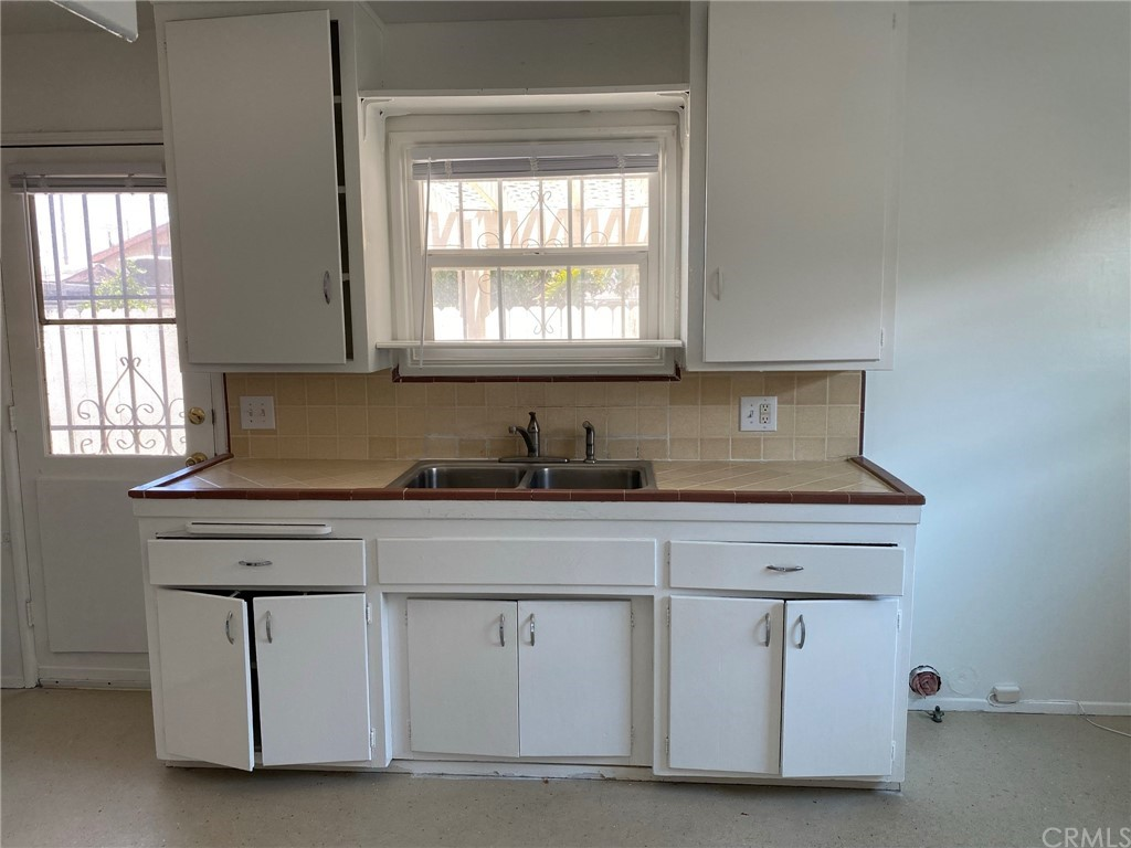 Kitchen with window view and door to private patio. This photo is a vacant unit on the left that shows the floor plan of the units for sale.