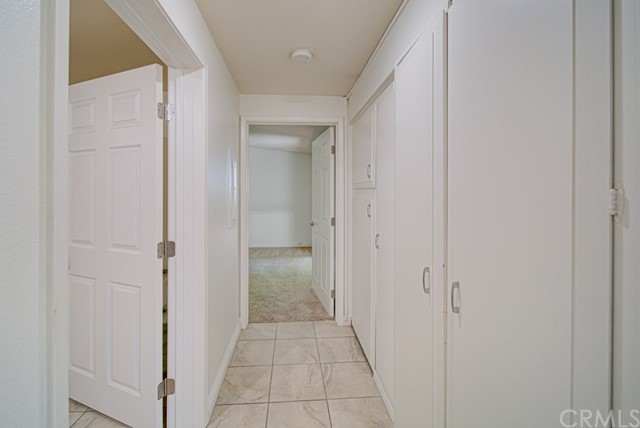 Hallway leading to the guest bedroom. Open door at left leads to Jack and Jill bathroom. Washer/dryer hookups are in closet at right.