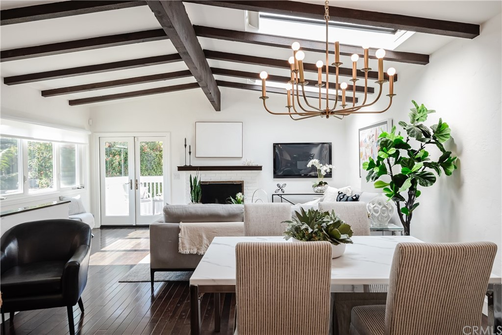 Designer Digs with a casual Spanish flare!  Greeted by an arched entryway and a striking dark and light vibe you enter the world of contrast: crisp white interior walls against the dark espresso wood floors and ceiling beams. The first floor is entry level and features a large master suite, two oversized closets with custom built-ins, the master bath and an access to the back yard. The ensuite bathroom is remodeled with imperial white marble floors and counter tops as well as double shower stalls and a custom bathroom vanity cabinet. The upper, second floor features vaulted ceilings with retractable skylights, a white brick fireplace in the living room, the dining area and the kitchen which has been appointed with custom cabinetry, quartz countertops and premium stainless steel appliances including a high-end Miele range with Dacor oven. There are two more bedrooms and a full bath upstairs with lots of light pouring in from the Eastern exposure.  The living area leads out to an outdoor patio overlooking the surprisingly spacious and very private back yard featuring turf and a fire-pit with built-in seating.  Property is updated with central air conditioning, double paned windows with plantation shutters, fresh paint inside and out, and much more!  This charming home is ideally located in a sweet spot near the tree-lined chip path otherwise referred to as the Green Belt and is within a short distance to Downtown Manhattan Beach, The Manhattan Village Mall and The El Segundo Point, LAX, and, of course, in is in the Award Winning Manhattan Beach School District.