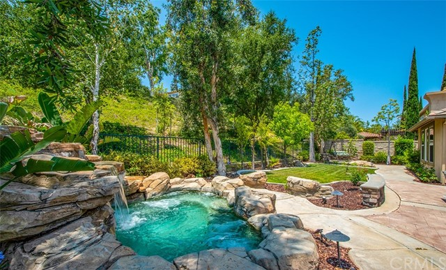 Absolutely Stunning Home! A MUST SEE!! Enjoy this luxurious Estate with handsome curb appeal and beautiful upgrades located in the prestigious 24-HR guard gated Summit Pointe Estates in Anaheim Hills. You will love this 5-BEDROOMS, 5.5-BATHROOMS - at nearly 3,970 sq ft this beautiful family home is elegantly appointed with style and comfort. The grand double door entry with a gracious staircase makes an impressive entrance and greeted with a beautiful open floor plan. This gorgeous home features a main floor master suite, master bath offers pure luxury, with double-sink vanity, jetted tub, walk-in shower and generous walk-in closet and an additional en-suite bedroom with retreat on the main floor is ideal for guest/in-laws or office. The impressive formal living room boasts a fireplace and high ceiling connects to the dining room. The kitchen is an entertainer's dream, with an oversized granite island with sit up seating, granite countertops, ample cabinets, stainless appliances including a built-in refrigerator, double ovens and a breakfast area. There is a lovely family room with cozy fireplace, surround sound and built-in entertainment center. The laundry room includes a sink and built-in cabinets. Additional features include built-in tech center, three and a half bath are upgraded, crown molding, water softener system, combination of wood/stone flooring, plantation shutters, dual A/C and two of the bedrooms in upper level has its own private bathroom and walk-in closet with organizer. Hang out at the beautifully landscaped backyard includes a waterfall cascading into a heated Pebble-Tec spa, built-in BBQ with bar seating that is perfect for entertaining. 2-car garage with built-in cabinets and over head storage. Good schools. conveniently close to shopping, dining and easy access to 91/241 FWY.