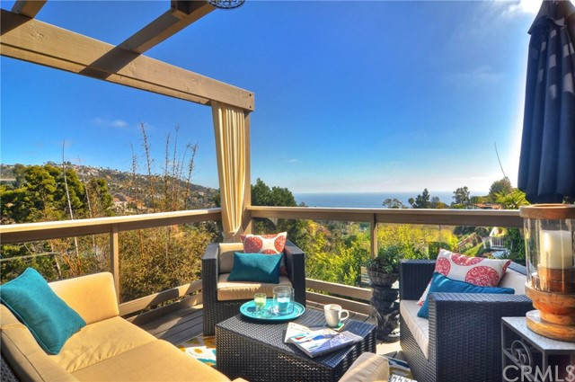 This gorgeous fully furnished ocean view home is beautifully decorated in a mid-century modern decor and features approximately 2800 sq ft of interior living space and over 1000 sq ft of outdoor living space making this truly an indoor/outdoor home. Featuring tumbled travertine flooring on the main level, home has a living room entrance with a dramatic stone fireplace that is open to the dining room and kitchen, flowing effortlessly onto the rear deck. The upper level of the home has new high end laminate hardwood-look flooring and on this level you will find the large master suite with retreat & balcony as well as three additional bedrooms (one used as an office). The lowermost level of the home features a large bonus room with an additional living room fireplace, bedroom alcove with murphy bed, bathroom and another large private deck. Additional features include an outdoor shower with both hot and cold water to rinse off after a day at the beach, a large grassy side yard and home is also air-conditioned for your comfort.