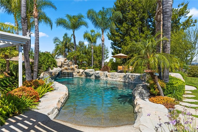Privacy and seclusion abounds! Desirable single level living and a tremendous resort backyard can be yours!  This gorgeous home boasts pristine curb appeal and is situated on a fully usable nearly half acre end of cul-de-sac lot. Freshly painted in soothing neutral tones, the versatile open floorplan offers walls of windows that bring the amazing backyard views in to this light and bright setting. Formal living and dining with French doors lead to the incredible outside. The granite kitchen is finished with stainless appliances, convenient center island and plentiful storage.  Family room with fireplace opens to sun-filtered patio.  Master bedroom wing is privately situated with fireplace, French doors leading to sunny patio, and a sumptuous master bath with dual vanity, and separate tub and shower. Three secondary bedrooms (one outfitted as office with built-ins, another bonus-room sized) plus a dual vanity bath complete the area. Stepping outdoors, you will be impressed by the lush landscaping that surrounds the property, a relaxing sun-filtered patio is ideal for morning coffee, evening meals, or watching family and friends tippy toe into the pool via the beach entry access, take a wild ride down the water slide, soothe cares away in the bubbling spa, or just sit, relax and enjoy the very private grounds and inviting city lights and hill views.    Sprawling grassy lawns, a bountiful veggie garden, and plentiful parking including RV access all complete the perfect package!