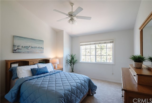 A secondary Bedroom on second level with vaulted ceiling and ceiling fan.