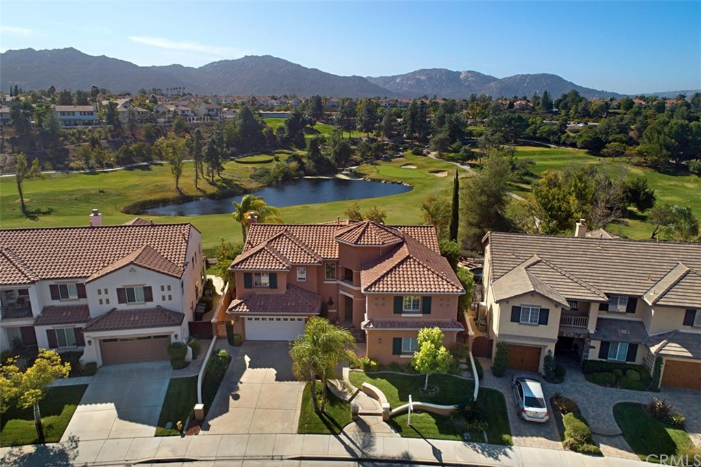 With a view of the 18th hole of Redhawk Golf Club and the setting sun over the mountains, this home in a gated community in Great Oak HS area is absolutely move in ready.  Ready for you with new flooring, new quartz kitchen counters, and new st/st appliances. Imagine preparing meals in this kitchen with vacation-like views!  This is an ideal floorplan with living/dining on one end of the large kitchen, and family room at the other.  Perfect for family life and for entertaining. The living/dining area has french doors to the pool and that view.  Family room has a beautiful fireplace and a wall of built-ins, and surround sound! The main floor bedroom with full bath is ready for guests.  Upstairs, enjoy the master suite through double entry doors, luxurious bathroom with soaking tub, and huge walk in closet with built ins.  Have morning coffee in the master retreat, and at the end of the day return to the master balcony to enjoy the sunset over the mountains and golf course! At the other end of the upper level is another family room with a full bathroom and two more bedrooms.  Great arrangement for children to have their own study/relax area.  This house has had one very caring owner who designed the back with artificial turf for easy care, and the front with superb lighting and a beautiful courtyard gate. The split 2 and 1 car garages both have epoxy flooring and lots of built in cabinets.  Wonderful community, exceptional home and lovely decor, all ready for its new owners.