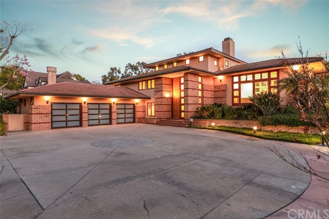 Once the home of Chapman University's President, this one-of-one Frank Lloyd Wright Prairie Style Inspired Estate is a dream! This three-story home perched perfectly on a hill hugs the circular driveway, as each story appears to overlap the other. The use of brick and a natural color palette creates a sense of balance & harmony that connects the home to the land upon which it stands. With 5 bedrooms & 5 bathrooms & over 4500 sqft set on 28,000+ sqft lot, this architectural masterpiece is designed for seamless entertaining. It's hosted everything from holiday dinners with family & friends, to fundraisers & concerts, and at one time the entire Chapman University Symphony Orchestra performing for 300 people. The kitchen features professional-grade appliances and overlooks a casual dining nook, central to the formal dining room & living room. A built-in bar accents the Great Room with fireplace & allows entertaining guests to seamlessly flow to the outdoors with separate dining & seating areas under multiple pergolas. The backyard is unmatched with beautiful landscaping, a large custom pool, spa, BBQ, and a separate shed built in the mid-century style of the home. The spacious Master Suite opens to 2 private decks overlooking the serene backyard. Separate office and guest quarters, wine cellar, library, garden area, 3-car garage...the list of features is endless. Located in prestigious Villa Park with award winning schools and easy access to all Southern California has to offer.