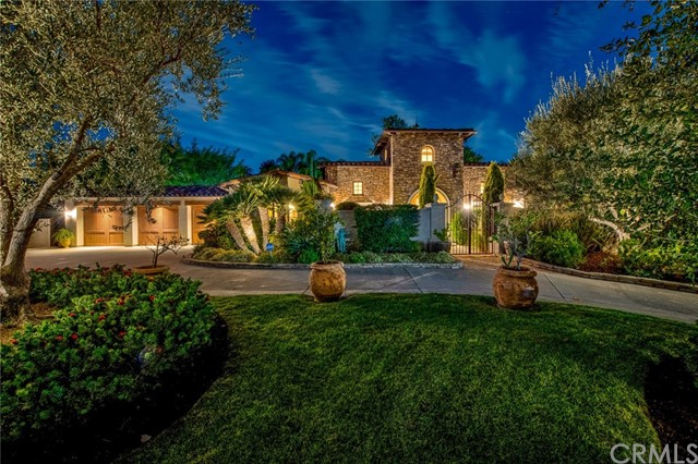 """Spectacular in every respect this custom-built Tuscan farmhouse single story home offers every luxury to the discerning buyer.  With 5000 plus square feet all on one level, with no ups or downs, this is a forever, one of a kind home.  Built in 2005 and virtually located on a cul de sac (as the street ends) every amenity has been considered.  With great curb appeal and a smooth stucco exterior, this home sits up from the street with a gated front courtyard and Italian garden.  A welcoming entry foyer sets the stage for both intimate living and entertaining.   This incredibly built and thought-out home features hand-hewn beams and solid core doors, custom windows, wood flooring and extra wide hallways.   The gorgeous and carefully planned Chef's center island kitchen includes elegant custom cabinetry,  dual built-in stainless Thermador refrigerator and freezer, double ovens, custom pendent lighting and is open to the Family room complete with exposed beam ceilings and massive fireplace with 6' tall crushed limestone mantle.   An adjoining Bonus/game room has two walls of windows and French doors that open to the inviting backyard. All bedroom suites are on right side of house with the immense resort style master suite offering every amenity and encompassing approx. 1100 sf.  For the car-collector, there is a three-car finished garage with enough height for a lift, epoxy flooring, custom cabinetry on three walls and hand-hewn massive headers above each door. There is a welcoming 500 sq. ft. loggia outdoors, built in true Italian Farmhouse style and custom-made dining table for 10 stays with the house.  An outdoor """"living room"""" with TV and two ceiling fans, plus kitchen with BBQ and serving bar with granite counter sets the stage for outdoor entertaining.  In addition this property offers a salt water pool and spa, raised bocci ball court, freestanding storage room and RV potential. Home also runs on the Savant automation system."""