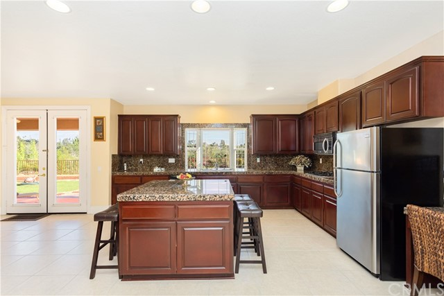 Beautiful Spacious Kitchen in Lower Level Home. Stainless Steel Appliances, Granite Counters, Built in Desk area, Wet Bar, Walk in Pantry, Recessed Lighting, Tile Flooring and French Doors leading to patio and backyard with Views!