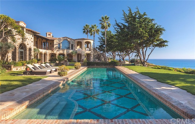 One of the most impressive oceanfront estates on the Southern California coast, this nearly three acre gated seaside compound sits on a scenic beach and renown surfing spot. Located in guard-gated Cotton Point Estates, this residence contains a multitude of spacious rooms within its nearly 13,000 square feet of living area. The expansive parcel with 450' of ocean frontage affords an eminently livable arrangement of these spaces that captures amazing garden, ocean and sunset views from every major room.One of the most impressive oceanfront estates on the Southern California coast, this nearly three acre gated seaside compound sits on a scenic beach and renown surfing spot. Located in guard-gated Cotton Point Estates, this residence contains a multitude of spacious rooms within its nearly 13,000 square feet of living area. The expansive parcel with 450' of ocean frontage affords an eminently livable arrangement of these spaces that captures amazing garden, ocean and sunset views from every major room. Grand two story spaces with beamed ceilings and intricate brick + stone walls are situated to take in ocean views through bronze framed windows. Limestone floors, walnut millwork, and Venetian plaster complement the architecture and setting. The rustic motif creates a casual elegance perfect for living and entertaining in this seaside setting. Highlights include an enormous master suite with sitting room + private terrace, 3 bedroom guest house, sport court, 55' oceanfront pool, event lawn, and a 9 car garage. The residence is surrounded by generous terraces, broad lawns and mature gardens set above the ocean. Designed without compromise, this offering includes every imaginable amenity in a setting that is private, spacious, and surrounded by ocean views.